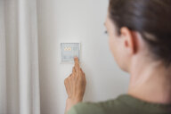 Woman using smart home switch on wall - DIGF05122