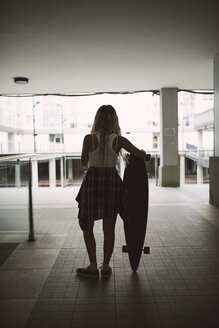 Young woman with her long board in a residential area - RAEF02147