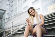 Young woman sitting on stairs, using smartphone - RAEF02150