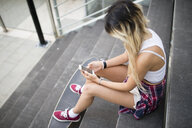 Young woman sitting on stairs, using smartphone - RAEF02153