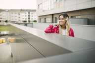 Portrait of a cheerful young woman leaning on a parapet - RAEF02162