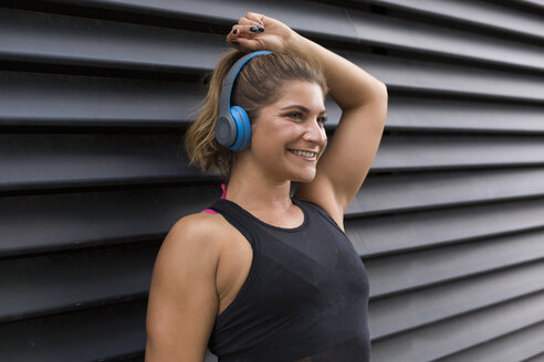 Portrait of smiling young woman listening music with headphones - JUNF01503