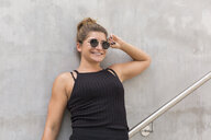 Portrait of smiling young woman wearing sunglasses leaning against concrete wall - JUNF01509