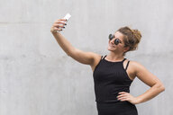 Portrait of smiling young woman dressed in black taking selfie with smartphone - JUNF01512