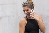 Portrait of laughing young woman on the phone - JUNF01515