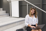 Portrait of smiling businesswoman sitting on stairs using laptop - JUNF01521