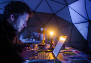 Man on expedition, using laptop in camp, Fletanes camp, Narsaq, Kitaa, Greenland - CUF46055