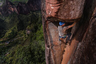 Rock climber climbing sandstone rock, elevated view, Liming, Yunnan Province, China - CUF46058