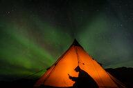Camper reading inside tent, Aurora Borealis in background, Narsaq, Vestgronland, Greenland - CUF46076