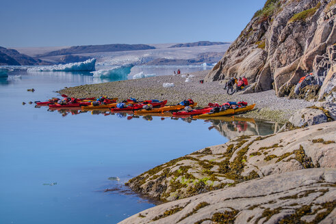 Adventure tourists on fjord beach with rows of kayaks, Narsaq, Vestgronland, South Greenland - CUF46094