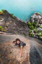 Man rock climbing on limestone rock, overhead view, Ha Long Bay, Vietnam - CUF46100