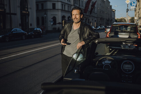 Mature man leaning on car, holding smartphone, Munich, Bavaria, Germany - JLOF00230