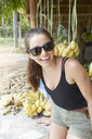 Young woman wearing sunglasses smiling by bananas - LUXF00878