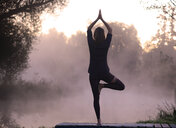 Woman practicing yoga by river at sunrise - LUXF00949