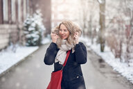 Smiling young woman walking along a snowy road - INGF00547