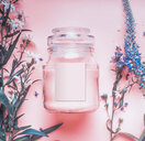 Close-up of a clear jar and flowering plants on a pink background - INGF00556