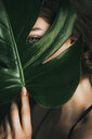Close-up shot of a woman holding a green leaf over her face - INGF00697