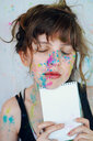 Young artist woman with paint in her face is holding a notebook - INGF00727