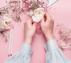 A human hand holding flowers against a pink background - INGF00775