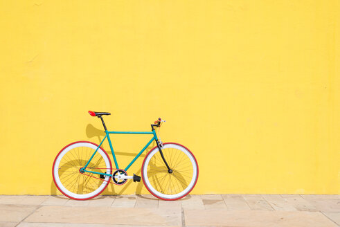 Side view of bicycle parked against a yellow wall with copy space - INGF00844