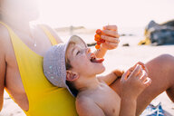 Cute happy little boy eating grapes at the beach - INGF00904