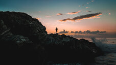 Silhouette person standing on cliff by sea against sky. - INGF01141