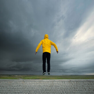 Rear view of a person jumping in a yellow rain mac on a cloudy day - INGF01240