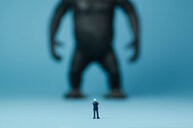 Rear view of a figurine standing against a blue background - INGF01333