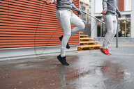 Male adult twins training, skipping with ropes on sidewalk - CUF46175