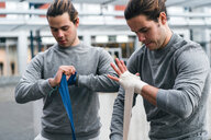 Identical male adult twin boxers training outdoors, bandaging hands with hand wraps - CUF46178