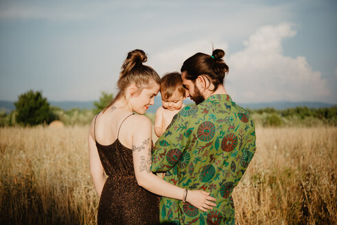 Couple with baby girl on golden grass field, Arezzo, Tuscany, Italy - CUF46208