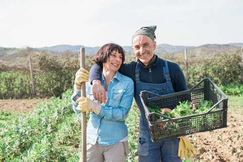 Mature couple with crate of vegetables in garden - CUF46235
