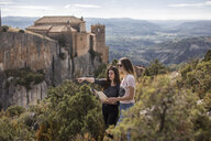 Spain, Alquezar, two young women with map on a hiking trip - AFVF01777