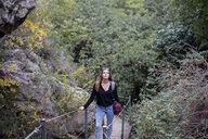 Spain, Alquezar, young woman on a hiking trip walking on boardwalk - AFVF01795