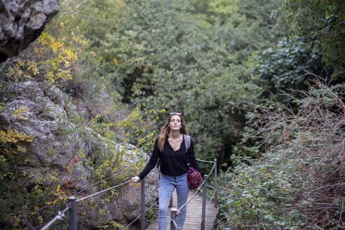 Spain, Alquezar, young woman on a hiking trip walking on boardwalk - AFVF01795