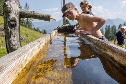 Boys at a well in mountainscape - HAMF00417
