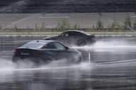 Two cars driving on wet surface on racetrack - HAMF00441