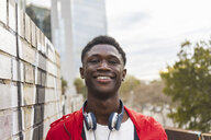 Young black man with headphones, smiling, portrait - AFVF01817