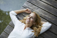 Smiling blond woman lying on wooden jetty at a lake - PNEF01012