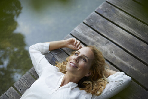 Smiling blond woman lying on wooden jetty at a lake - PNEF01015
