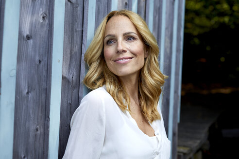 Smiling blond woman in front of wooden wall - PNEF01018