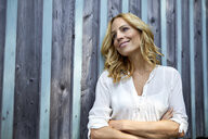 Smiling blond woman in front of wooden wall - PNEF01021