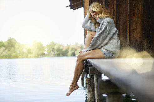Smiling relaxed woman sitting on wooden jetty at a lake - PNEF01024