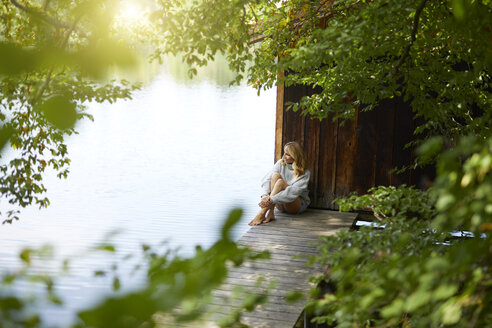 Relaxed woman sitting on wooden jetty at a remote lake - PNEF01027