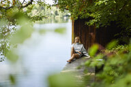 Relaxed woman sitting on wooden jetty at a remote lake - PNEF01033