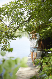 Smiling woman standing on wooden jetty at a remote lake - PNEF01036