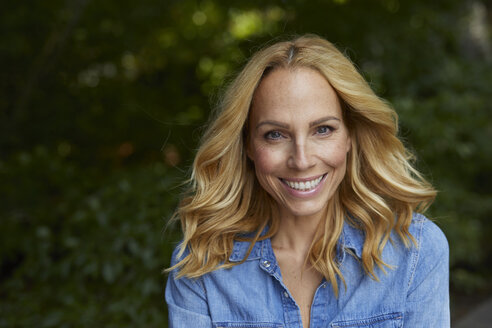 Portrait of smiling blond woman outdoors - PNEF01039