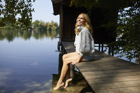 Relaxed woman sitting on wooden jetty at a remote lake - PNEF01042