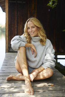 Smiling relaxed woman sitting on wooden jetty at a lake - PNEF01045