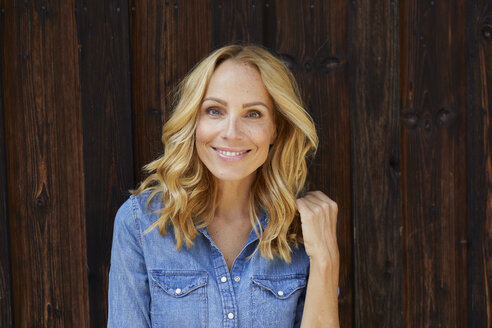 Portrait of smiling blond woman in front of wooden wall - PNEF01048